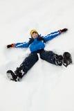 Junger Junge, der Schnee-Engel auf Steigung bildet Stockfotos