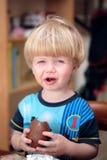 Junger Junge, der Schokolade Osterei isst und genießt Stockfotos