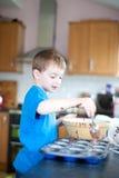 Junger Junge, der Schokoladenkuchen bildet Stockfotografie
