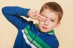 Junger Junge, der sein Auge abdeckt. Lizenzfreie Stockfotografie