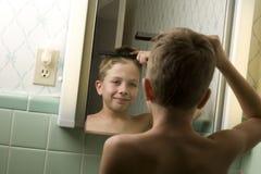 Junger Junge, der sein Haar kämmt stockbild