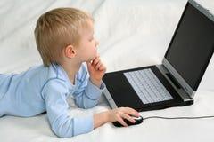 Junger Junge, der seinen Laptop verwendet Lizenzfreie Stockfotografie