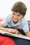 Junger Junge, der sich auf seinem Bett liest ein Buch hinlegt Stockfotos