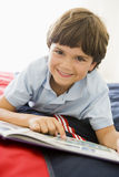 Junger Junge, der sich auf seinem Bett liest ein Buch hinlegt Lizenzfreies Stockfoto