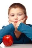 Junger Junge, der sich entscheidet, einen Apfel zu essen Stockbilder