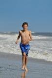 Junger Junge, der am Strand läuft Lizenzfreie Stockfotos