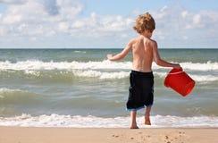 Junger Junge, der am Strand spielt Lizenzfreie Stockfotos