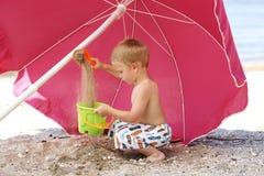 Junger Junge, der am Strand spielt Stockbild