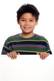 Junger Junge, der unbelegtes Zeichen anhält Stockbilder