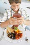 Junger Junge, der ungesundes gebratenes Frühstück isst Lizenzfreie Stockbilder