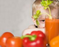 Junger Junge, der unter Gemüse sich versteckt Lizenzfreies Stockfoto