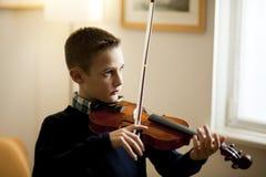 Junger Junge, der Violine spielt Lizenzfreie Stockfotos