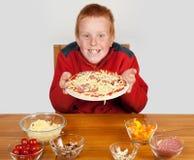 Junger Junge, der weg gebildete Pizza zeigt lizenzfreies stockfoto