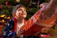 Junger Junge, der Weihnachtsgeschenk empfängt Stockfotografie