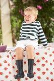 Junger Junge, der Wellington-Matten trägt Stockfoto