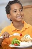Junger Junge, der zu Hause eine Mahlzeit genießt stockfotos