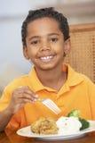 Junger Junge, der zu Hause eine Mahlzeit genießt Stockfotografie