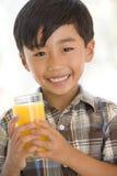 Junger Junge, der zuhause das Orangensaftlächeln trinkt Lizenzfreies Stockfoto