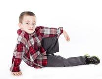 Junger Junge im Plaidhemd, das auf seine Seite legt Lizenzfreies Stockfoto
