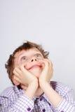 Junger Junge, der aufwärts überrascht schaut und auf grauem Hintergrund lächelt Lizenzfreie Stockfotografie