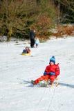 Junger Junge im Schlitten, der schneebedeckten Hügel, Winterspaß schiebt Lizenzfreie Stockfotografie