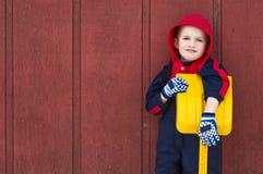 Junger Junge lehnt sich auf seiner Spielzeugschaufel lizenzfreie stockfotos
