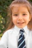 Junger Junge mit dem langen Haar im weißen Hemd und in der Gleichheit stockbild