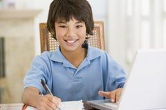 Junger Junge mit dem Laptop, der Heimarbeit tut Lizenzfreie Stockbilder