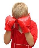 Junger Junge mit den Händen in den roten Handschuhen auf seinem Gesicht. Stockfotografie