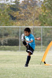 Junger Junge mit einem großen treten innen Fußball Stockfoto