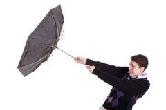 Junger Junge mit einem Regenschirm drehte sich durch den Wind Stockfotos