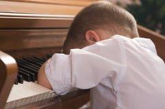 Junger Junge mit Kopf auf dem Klavier Lizenzfreie Stockfotografie