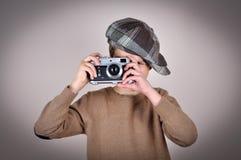 Junger Junge mit Retro- Kamera Stockfoto