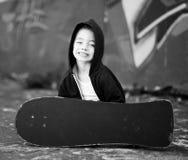 Junger Junge mit Skateboard gegen eine Graffitiwand Stockfoto