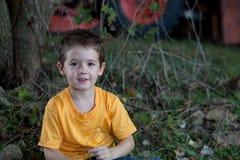 Junger Junge mit Traktor im Hintergrund Stockfotos