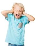 Junger Junge schreit und deckt Ohren ab stockfoto