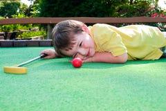 Junger Junge spielt Minigolf lizenzfreie stockfotografie