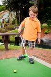 Junger Junge spielt Minigolf Stockfoto