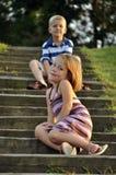 Junger Junge und das Mädchen, die auf Park sitzt, tritt Stockfoto