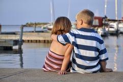 Junger Junge und Mädchen, die in einem Jachthafen sitzt Lizenzfreies Stockfoto