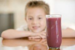 Junger Junge zuhause mit Fokus auf Saftglas Lizenzfreies Stockfoto