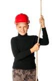 Jungenerbauer im Sturzhelm, der ein Seil hält Stockbild