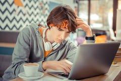 Junger Juniorprogrammierer, der auf der schwierigen Aufgabe denkt lizenzfreies stockfoto