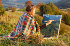 Junger Künstler, der eine Herbstlandschaft malt Lizenzfreies Stockfoto