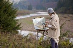 Junger Künstler, der eine Landschaft malt Lizenzfreies Stockfoto