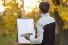 Junger Künstler malt ein Bild auf Segeltuch auf einem Gestell in der Natur, ein Mann mit einer Bürste und eine Palette von Farben stockfotografie