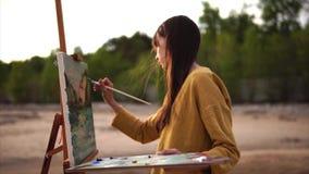 Junger Künstler zeichnet ein Palettenmesserstillleben, welches das Mädchen nahe dem Meer oder den Flüssen ist stock footage
