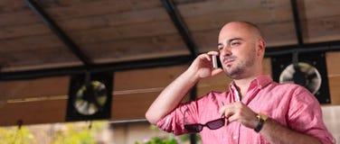 Junger kahler Mann, der am Telefon - Briefkasten spricht Lizenzfreie Stockfotografie