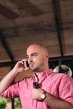 Junger kahler Mann, der am Telefon - Vertikale spricht Stockfoto