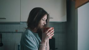Junger kalter Mädchenblick im Fenster und im Getränkkaffee in der Küche am Morgen stock video footage